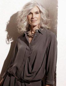 Mulher bonita com cabelos grisalhos e bem vestida está sorridente.
