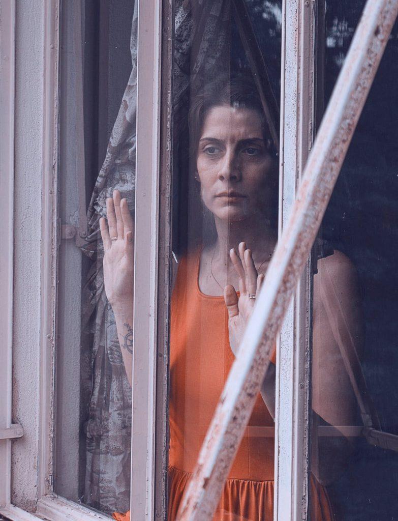 Mulher+50 Insatisfação, tristemente olha pela janela.