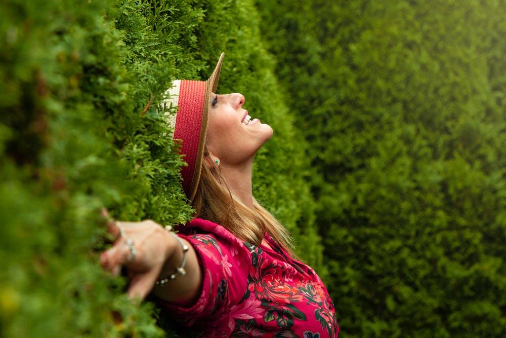 Mulher de 40 anos está encostada a uma cerca viva , sorridente.