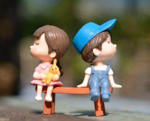 Um boneco menina e um boneco menina estão sentados num banco sem se olhar,sugerindo que casamento e perimenopausa.