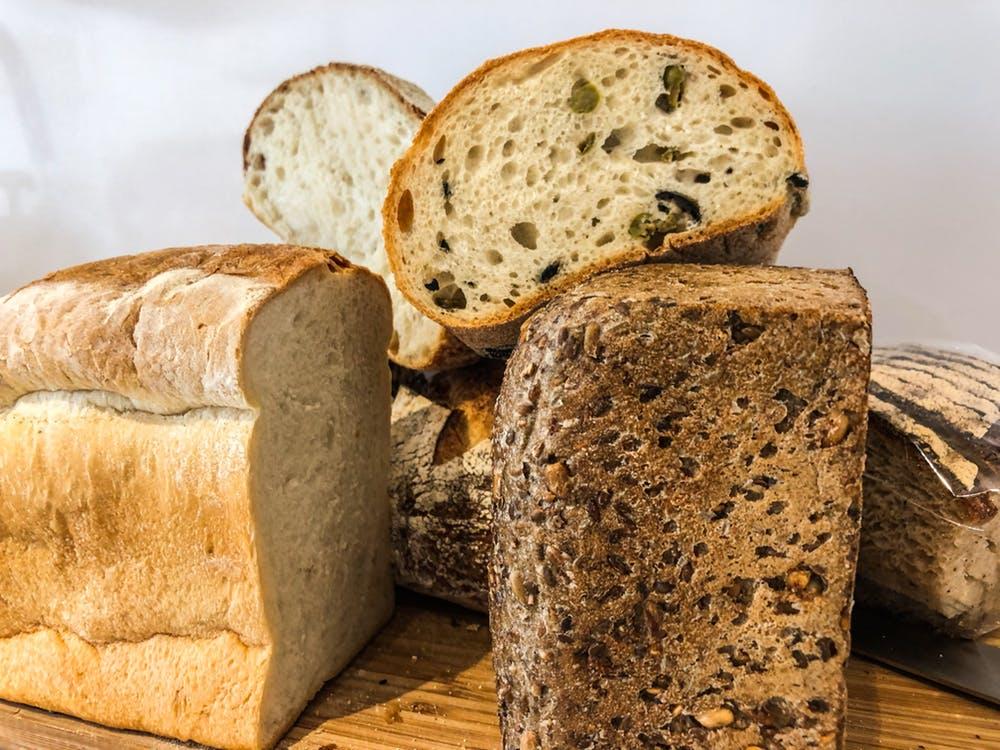Vários tipos de pães partidos ao meio estão sobre uma tábua de madeira.