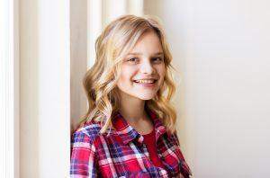 Menina loira de 12 a 13 anos de idade , encostada na parede, sorri.