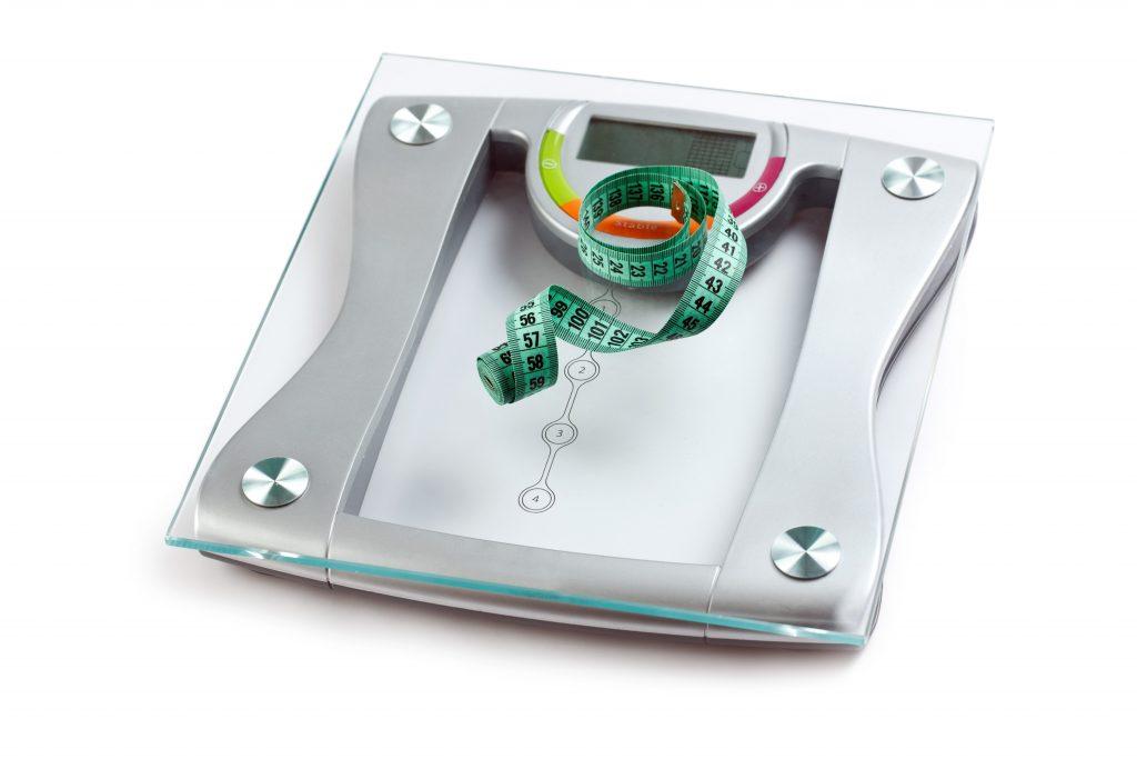 Uma balança e uma fita métrica lembram a importância de se manter o peso na Menopausa