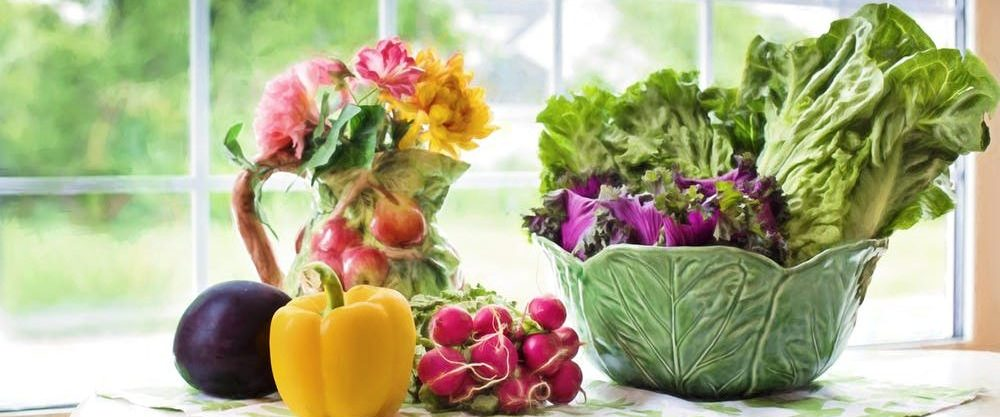 Bancada em frente a uma grande janela expõe um jarro com flores, uma tigela grande com verduras.