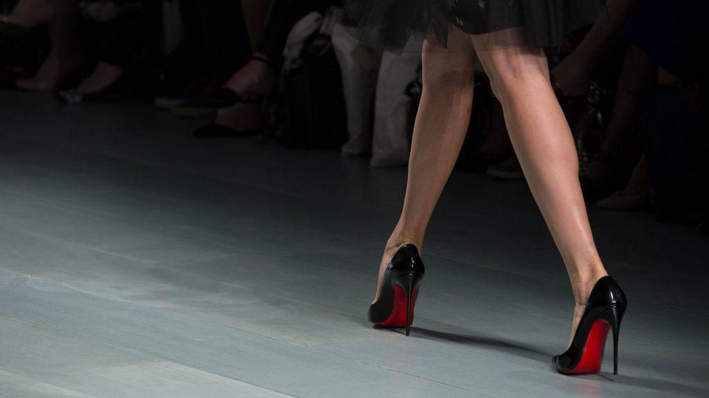Modelo desfila sapatos de salto alto.