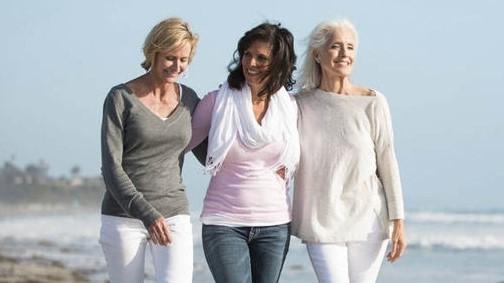 Três mulheres de meia-idade caminham à beira-mar.