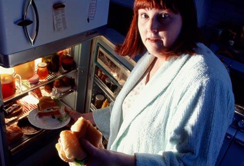 Mulher gordinha de +30 anos ataca o refrigerador para comer à noite, sugerindo que o casamento pode fazer engordar.