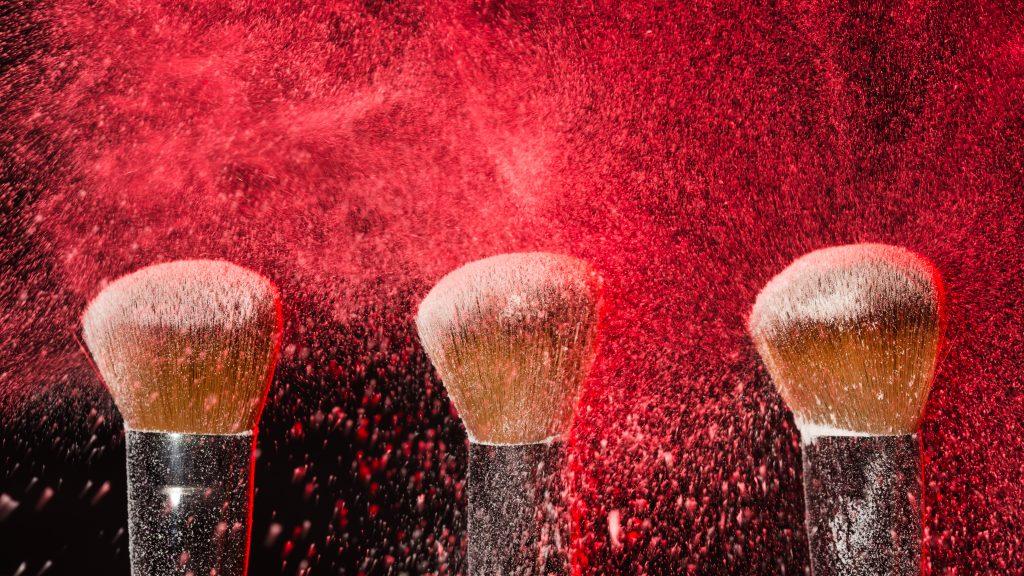 Três pincéis para aplicar blush estão lado a lado e envoltos em uma névoa de vermelho-maquiagem valoriza a mulher.