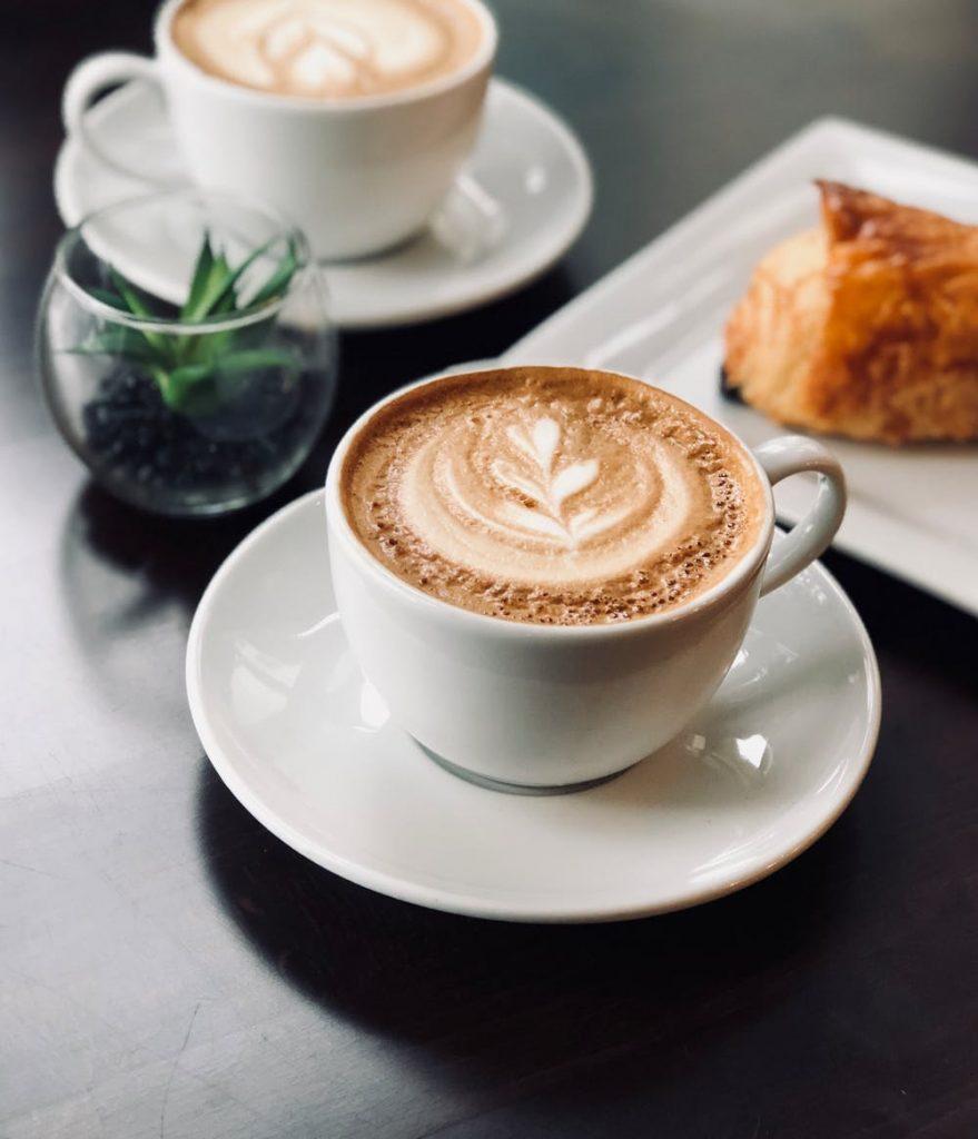Bela xícara de café e um delicioso croissant estão sobre uma mesa e dificultam emagrecer depois dos 40 .