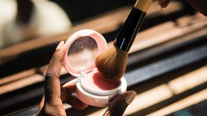 Mulher coloca um largo pincel de maquiagem sobre a embalagem de blush.
