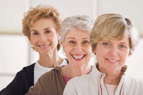 Três mulheres sorridentes não tem sintomas da menopausa.