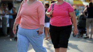Duas mulheres obesas caminham ao sol pois tomar sol emagrece.
