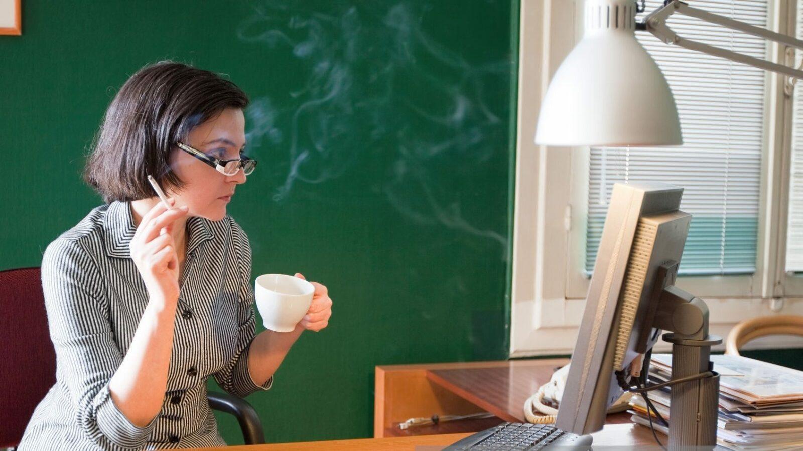 Mulher fuma e toma café enquanto trabalha.